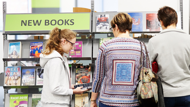 Two women and teen girl looking at new books