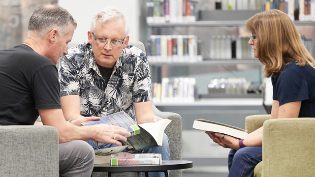 Three adults sharing books