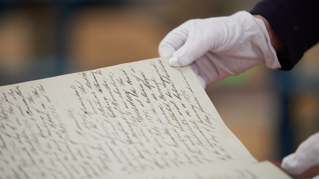 Hands in gloves turning page of old book