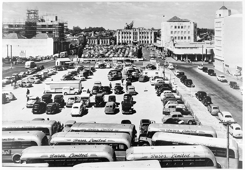 Cars and buses in a large carpark circa 1950s