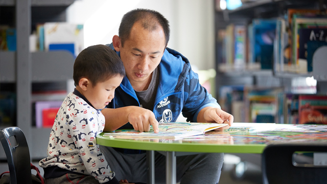 Man and child reading book at table