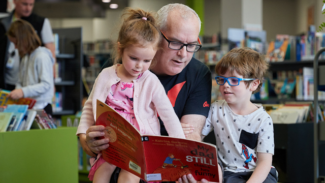 Image of a father reading a picture book to his son and daughter at Central Library in the children's area.