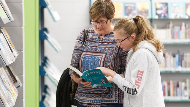 Image of a mother and daughter looking at a book.